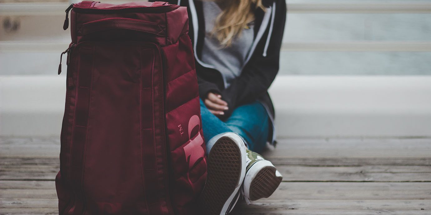 Girl sitting next to a large backpack