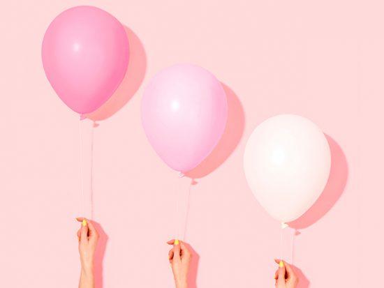 Women's Hands Holding Pink Balloons
