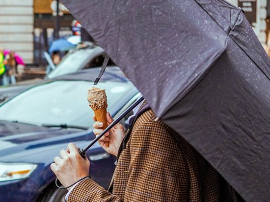 Woman Eating Ice Cream and Holding an Umbrella