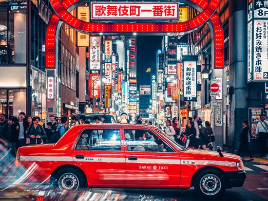 City streets of Tokyo at night, taxi driving past.