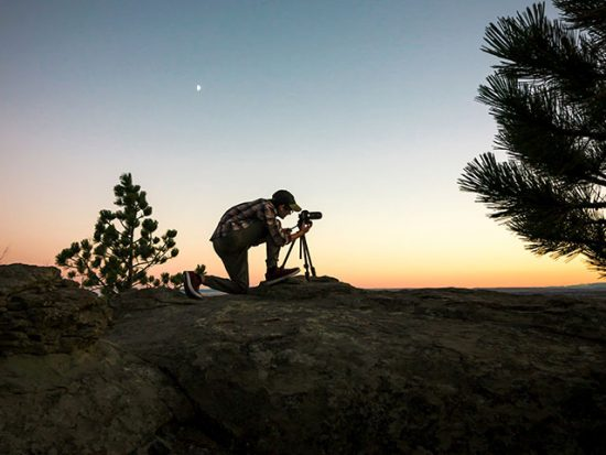 Man at sunset taking a photo with a camera on a tripod