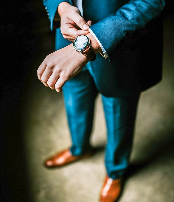 Man in a Blue Suit Fastening his Watch