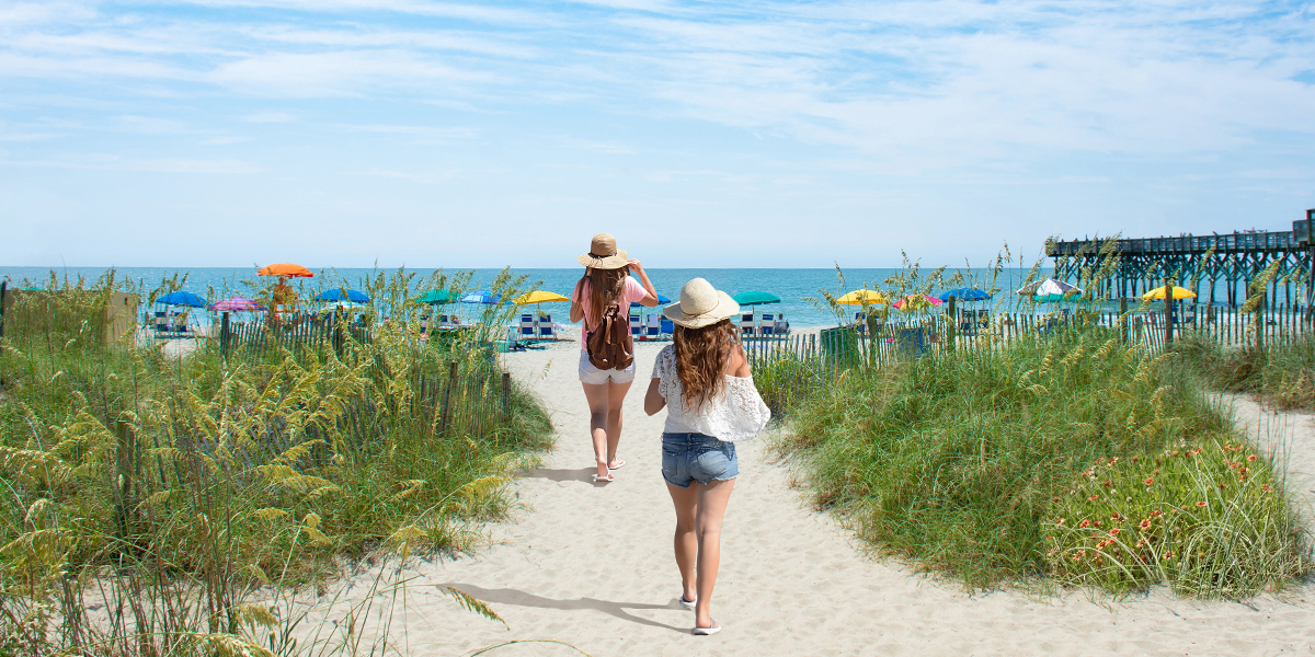 Two girls walking onto the beach in Myrtle Beach, South Carolina.