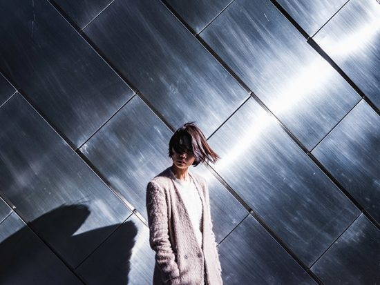 Woman in Tokyo standing in front of a reflective wall.