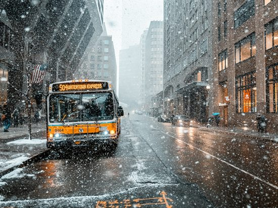 Boston street in winter, snow falling and a bus in the street.
