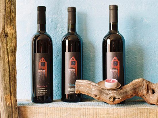 Three wine bottles on a shelf.
