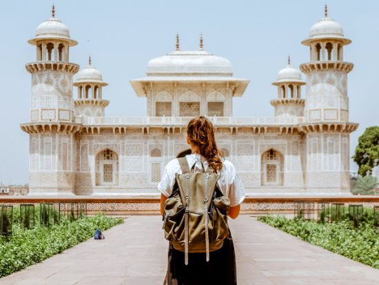 Woman standing in front of an ornate building in Agra.