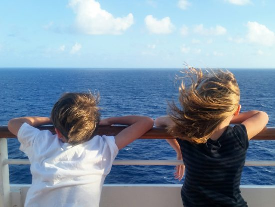 Kids looking out at the sea from a cruise ship.