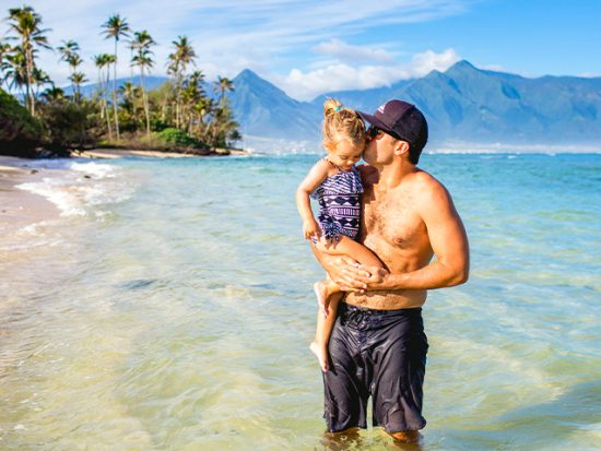 Man Holding His Daughter on a Beach.
