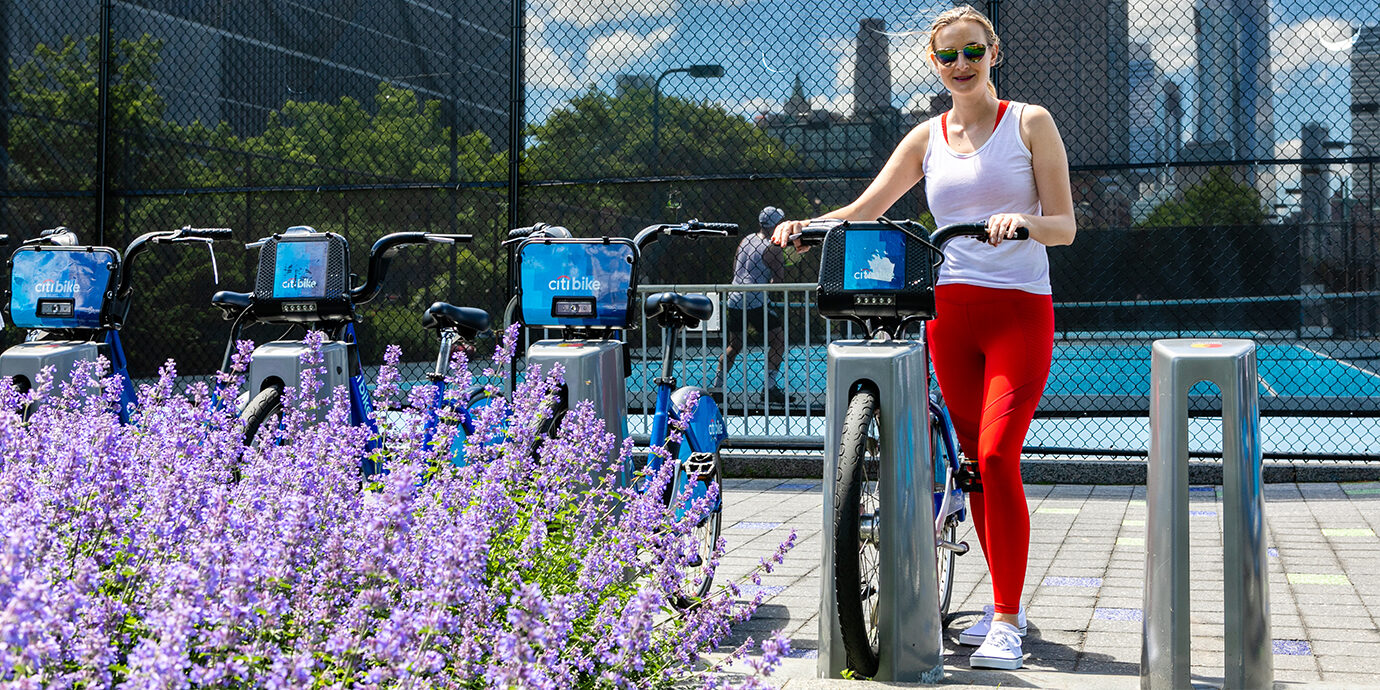 Megan getting a CitiBike while wearing Fabletics leggings.