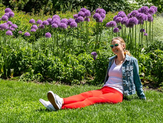 Megan sitting in the grass with flowers, wearing Fabletics.