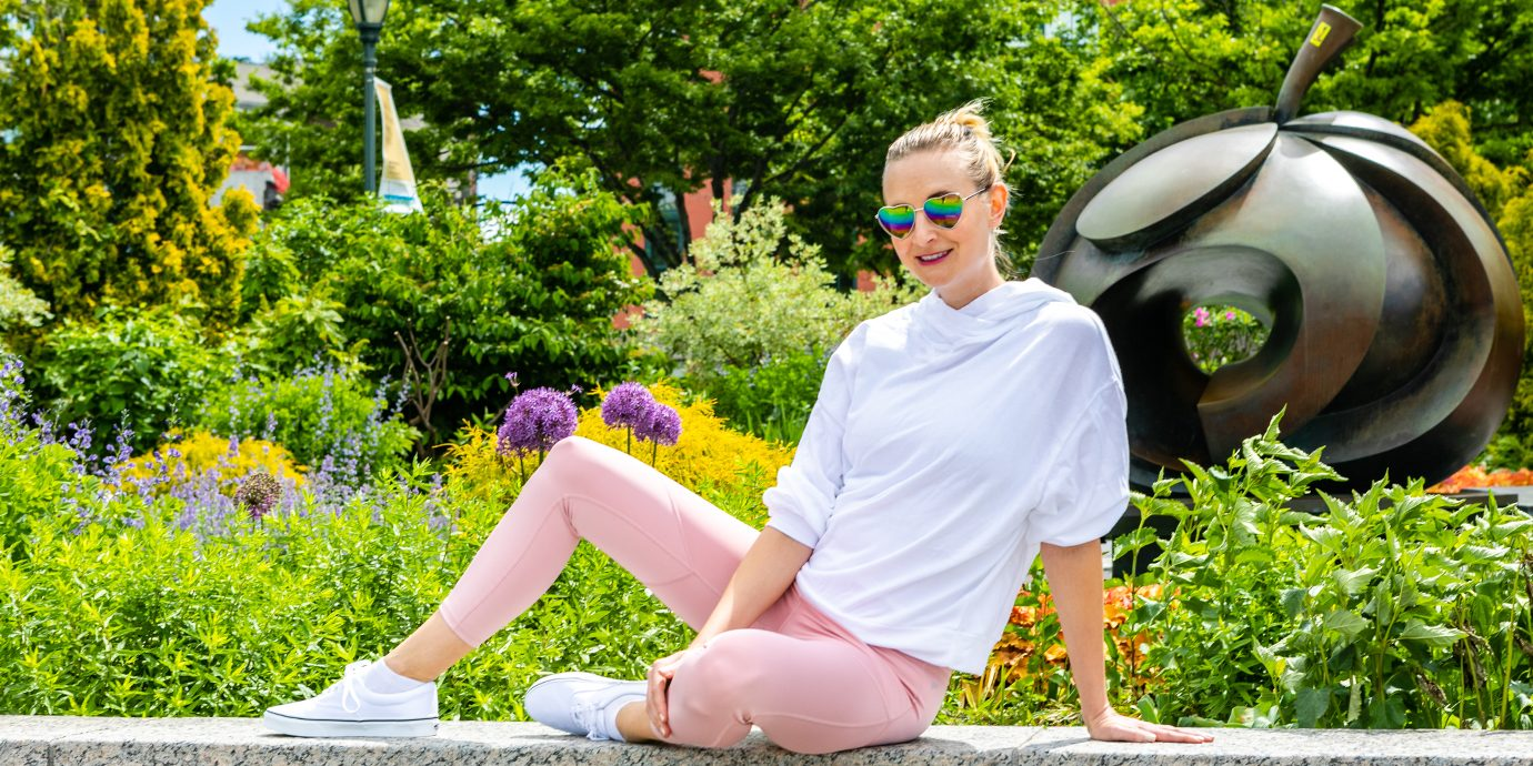 Megan wearing a pair of pink leggings lounging in front of flowers.