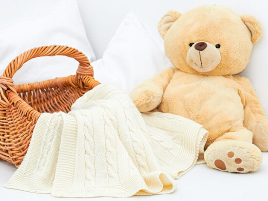 Teddy bear and blanket on a bed.