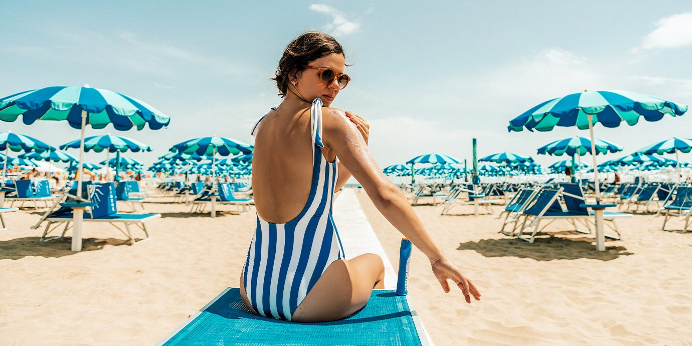 Woman Putting Suncreen on while sitting on the beach.