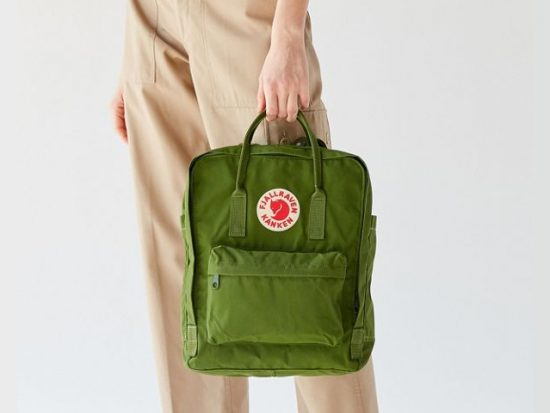 Woman holding a Fjallraven Kanken Backpack.
