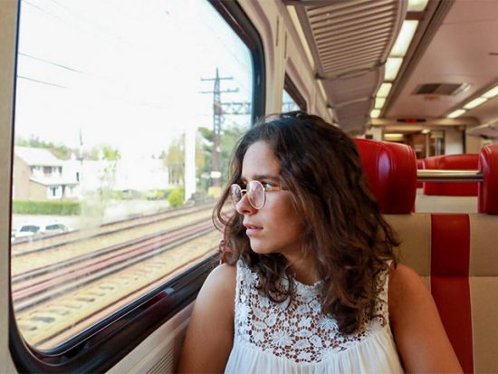 Woman sitting on a train looking out the window.