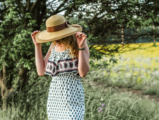 Woman wearing a Sun Hat standing in a field.
