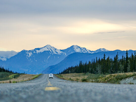 Car driving down the road at sunset in Alaska.