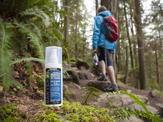 Man hiking with Sawyer Products SP543 Premium Insect Repellent.