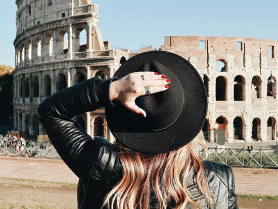 Woman Standing in front of the colisseum.