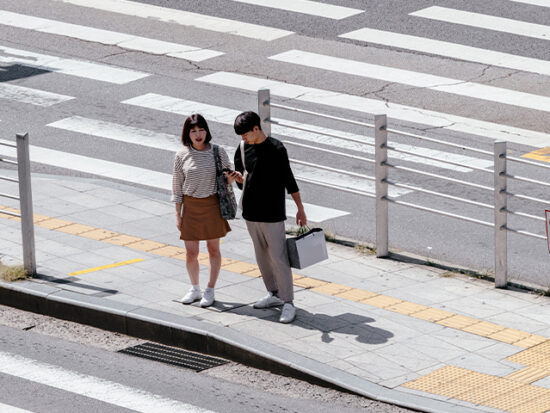 Couple in Seoul South Korea waiting to cross the street.