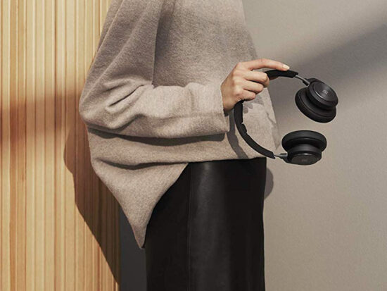 Woman Holding Bang & Olufsen Beoplay H9 3rd Gen Wireless Bluetooth Over-Ear Headphones.
