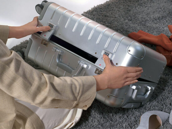 Person Closing the Away Aluminum Carry-On Suitcase.