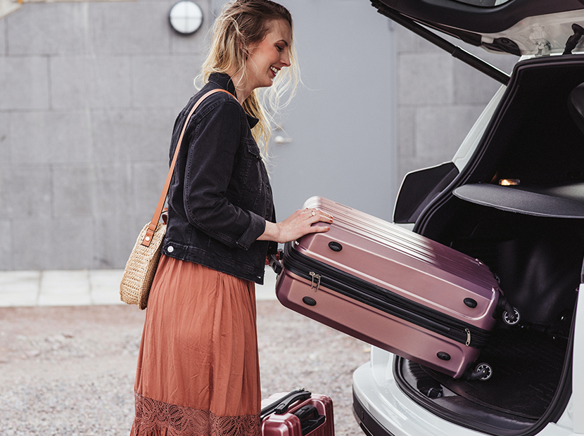 Woman putting two suitcases into the car.