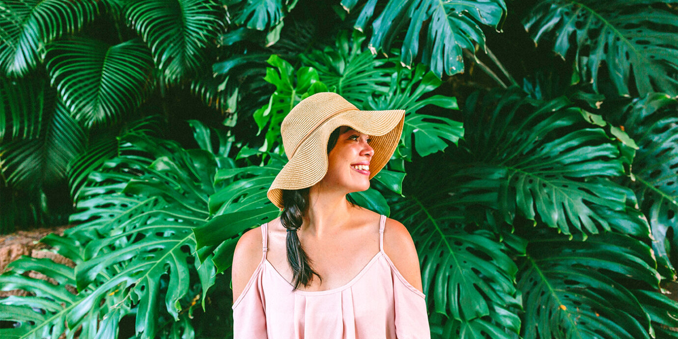 Woman standing in front of Monstera plants.