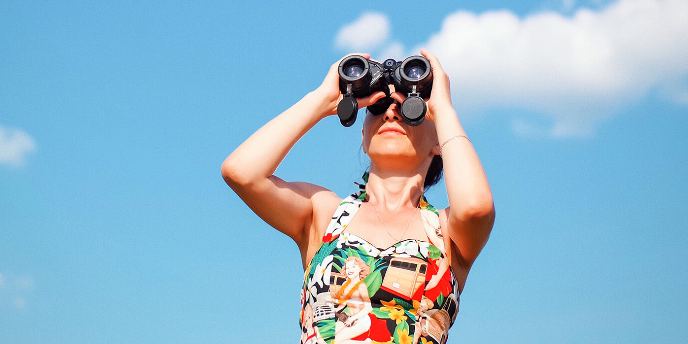 Woman standing looking through binoculars.