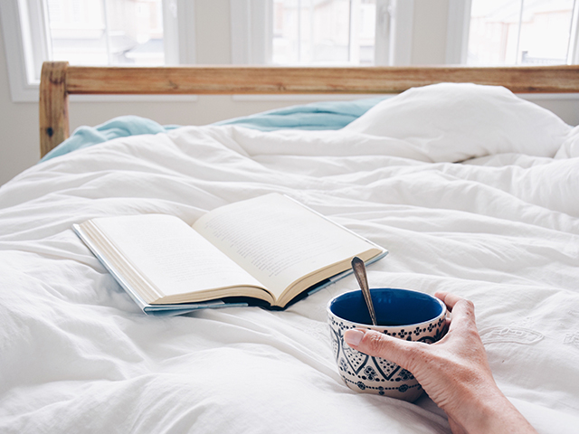 Book laying on bed and woman holding a coffee cup.